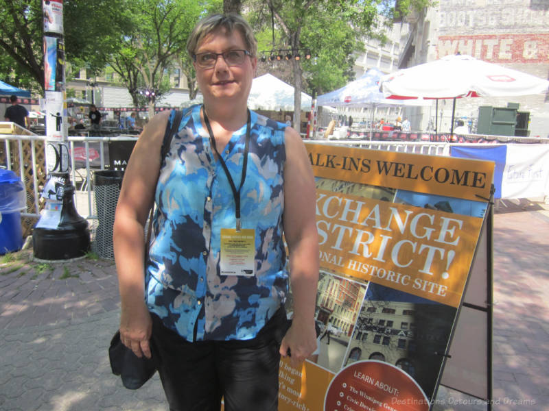 Standing beside a tour sign in a heritage district before embarking on a walking food tour