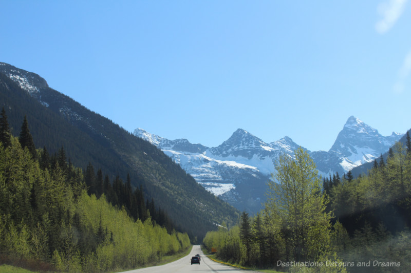 Highway through majestic snow-capped forested mountains