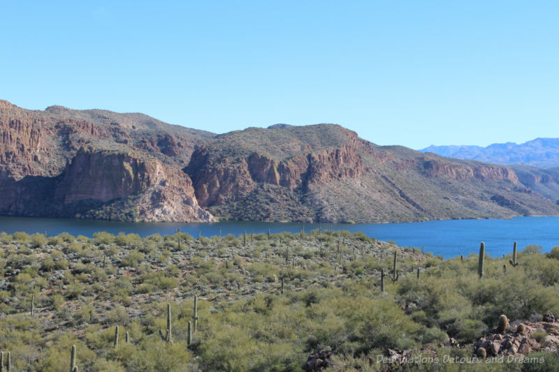 View of blue lake surrounded by cacti-covered mountains