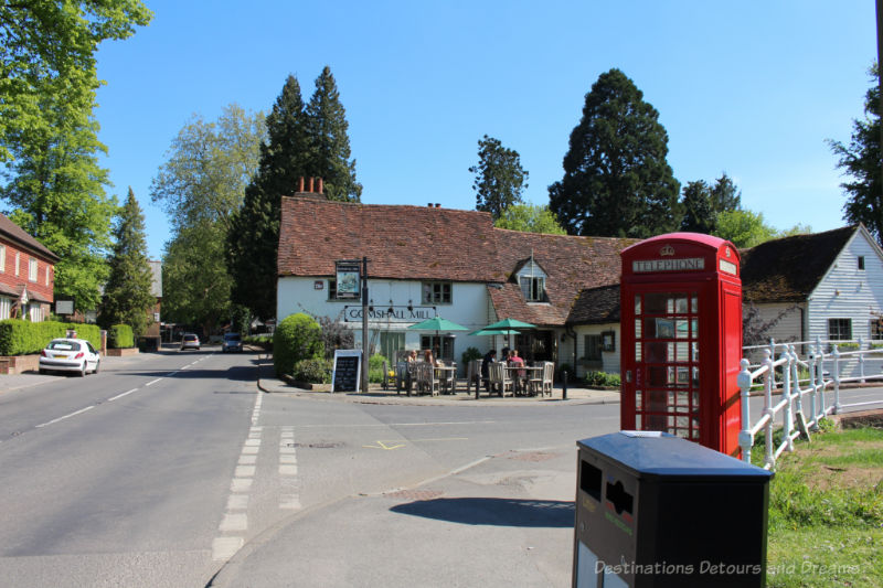 A crossroads in an English village with a red telephone booth and old mill turned restuarant