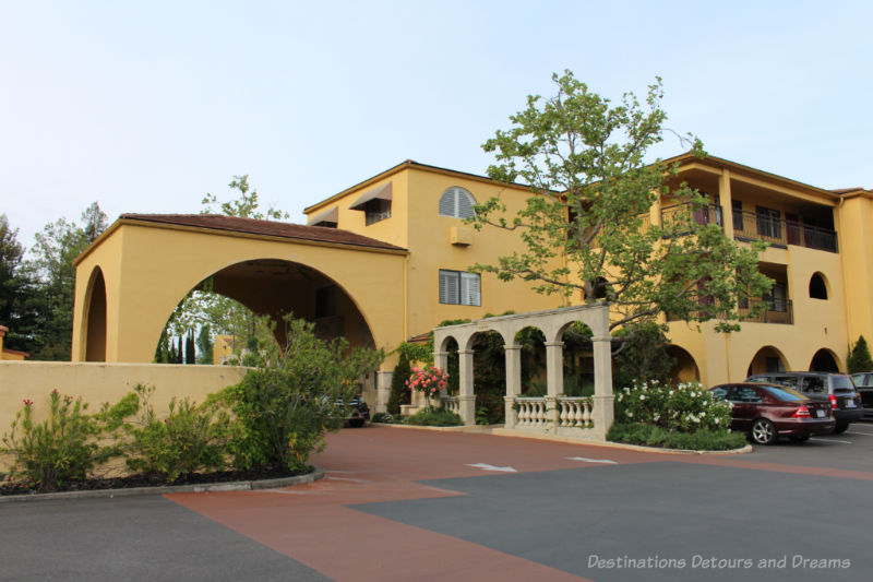 A Mediterranean-themed two-story hotel with yellowish stucco finish and covered drive-up