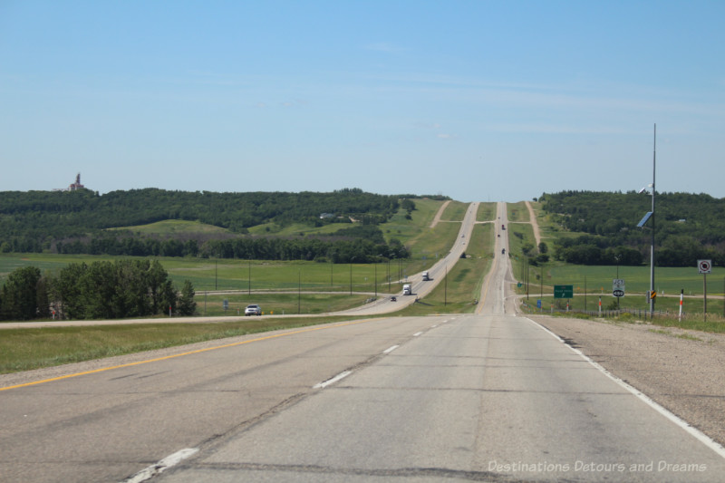 Road Trip Tips - a divided highway going into and out of a small valley on the prairies