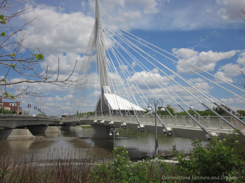 A cable-stayed pedestrian bridge crossing a city river