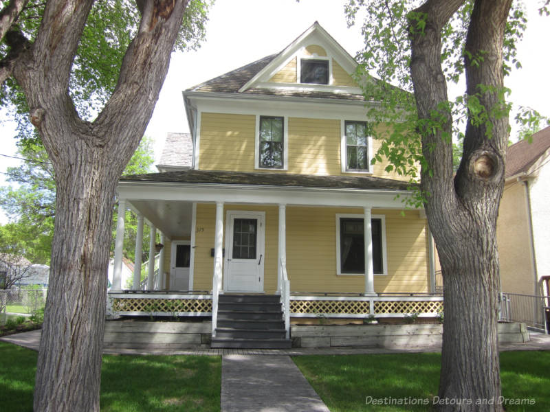 Early 1900s two-story wood house - yellow with white trim - wrap-arpund porch with white columns and lattice railing
