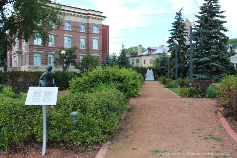 Path into a landscaped sculpture garden beside an early 1900s red brick building in Saint Boniface, Winnipeg