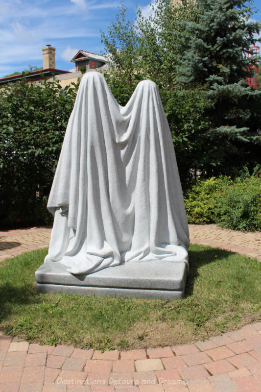 A sculpture showing two figures draped in white cloth