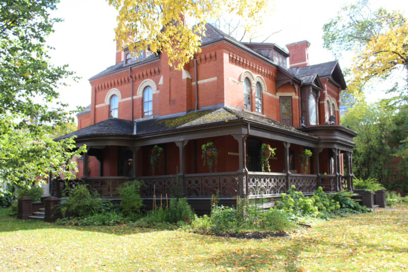 A red brick Victorian mansion with wood wrap-around porch