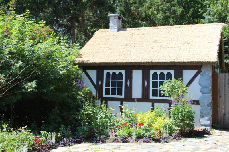 Small cottage with thatched roof, white walls, and brown wood trim in the middle of a garden