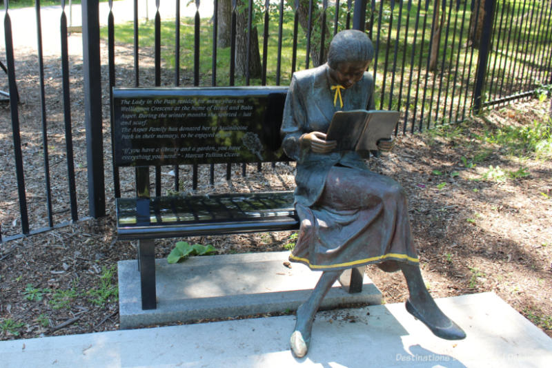 A statue of a woman sitting at one end of a park bench reading a book