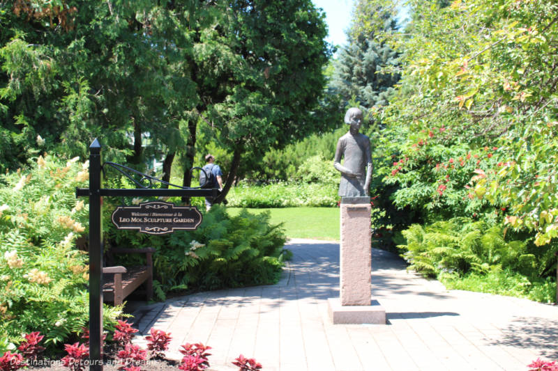 Sculpture of a school girl on a pedestal along a stone pathway surrounded by trees and shrubs at the entrance to a sculpture garden