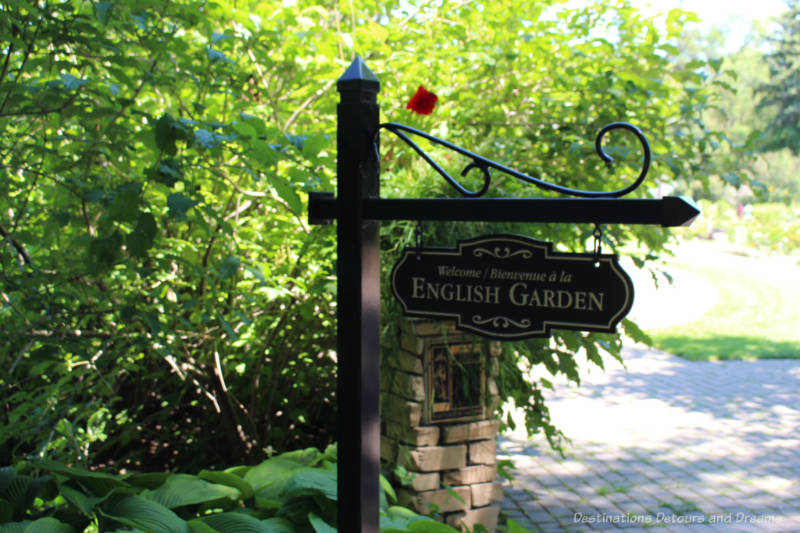 Signpost welcoming to English Garden in front of greenery