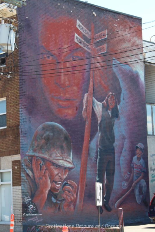 Murals in shade of red, grey, and purple showing actor Adam Beach as himself and as some of his roles