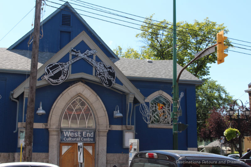 Blue building with musical cutouts decorating windows and the area above the door