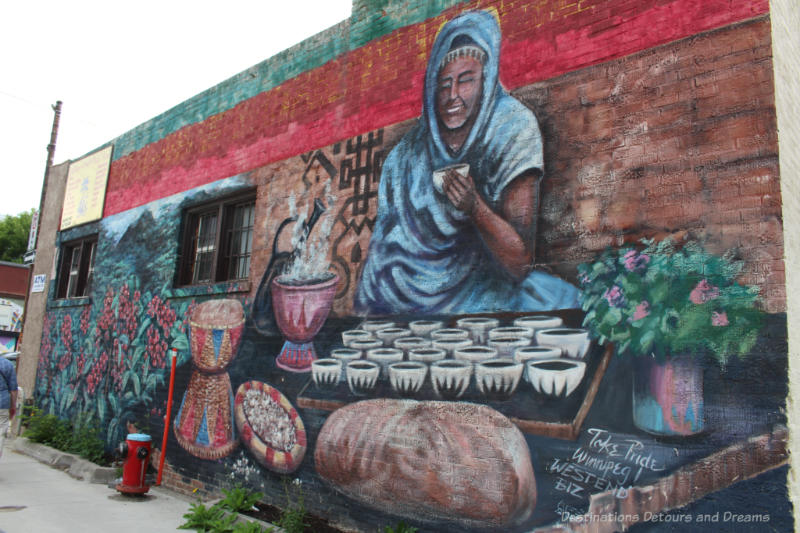 Mural showing Ethiopian women in front of tray of coffee cups with coffee brewing and coffee plants to her right