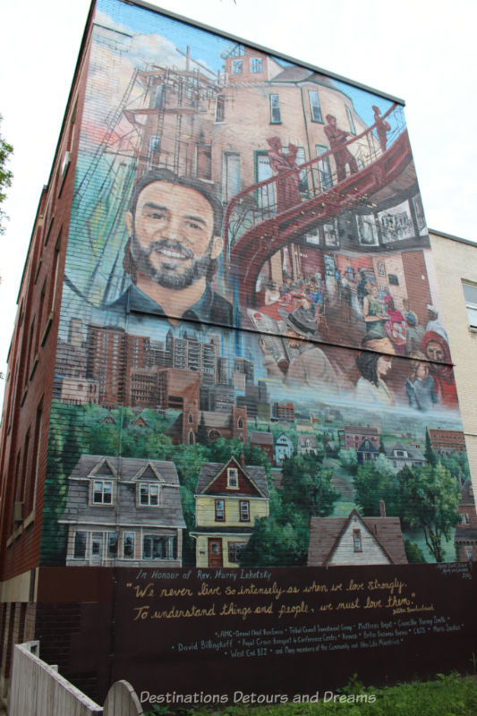 A mural containing a collage of items around the face of the many it commemorates such as housing in the city, food service