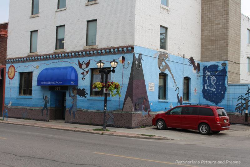 Mural with blue background painted on front and side of a building with Canadian aboriginal symbols