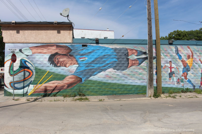 Mural with soccer plays, one of whom is horizontal across the wall reaching for a World Cup ball