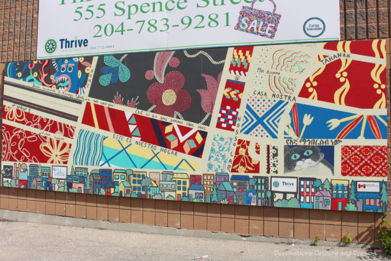 Mural shows street map as a quilt with colourful textiles from various countries forming the blocks