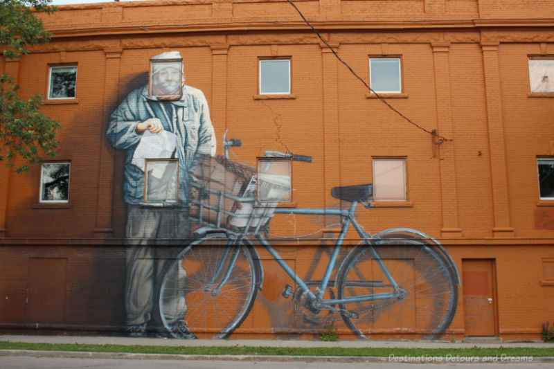 Mural of a large man beside his bicycle on an orange wall