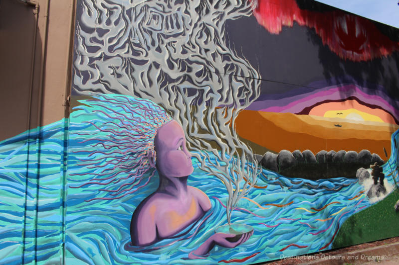 Part of a mural featuring a stylized person with flowing blue-green hair representing bodies of water doing a sage grass smudge again a background of rocks and coloured sky.
