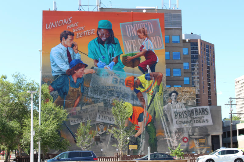 A several story high mural with a collage of scenes representing the history of the Manitoba labour movement from the Winnipeg 1919 General Strike to present day.