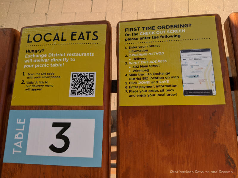Instructions on a patio table with QR codes for ordering food
