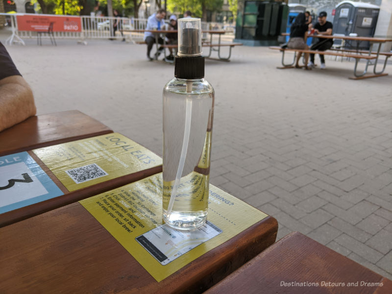 A spray bottle of hand sanitizer on a public patio picnic table