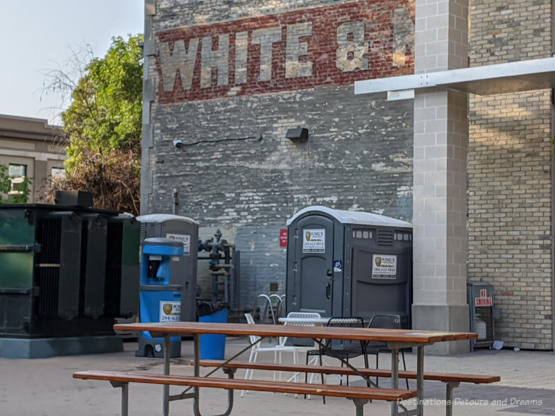 Portable toilets and hand washing station on a public patio in front of an old brick building