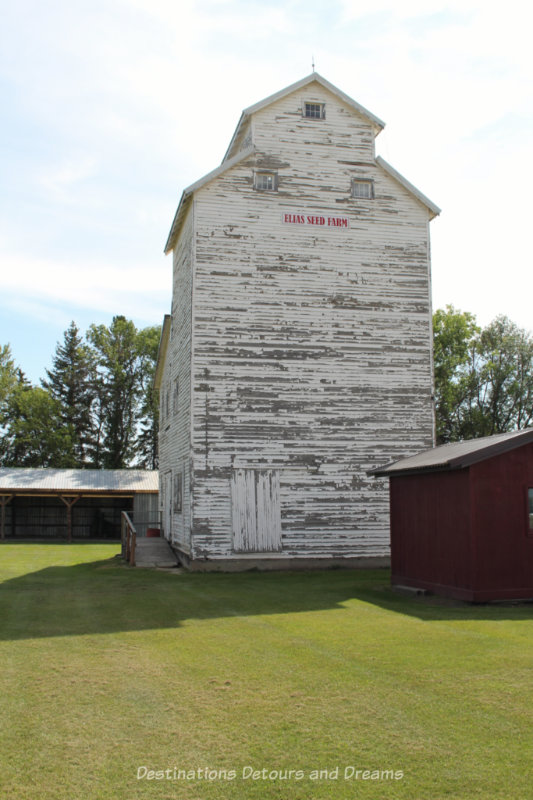 Weathered white wooden grain elevator at an outdoor museum