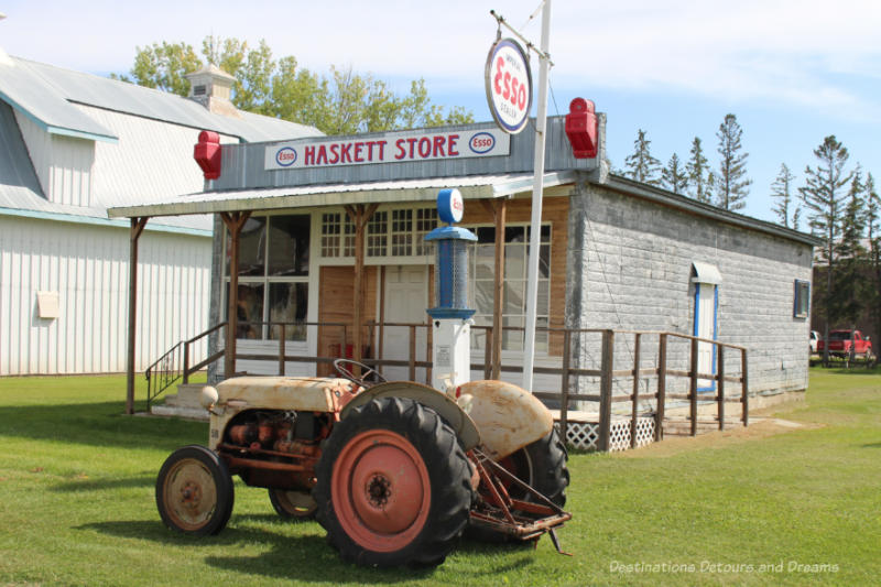 Rusted tractor in front of an old one-story store with an old Esso gas pump