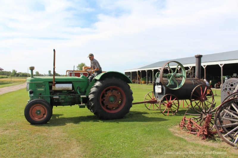 Man on a vintage tractor pulling a steam engine