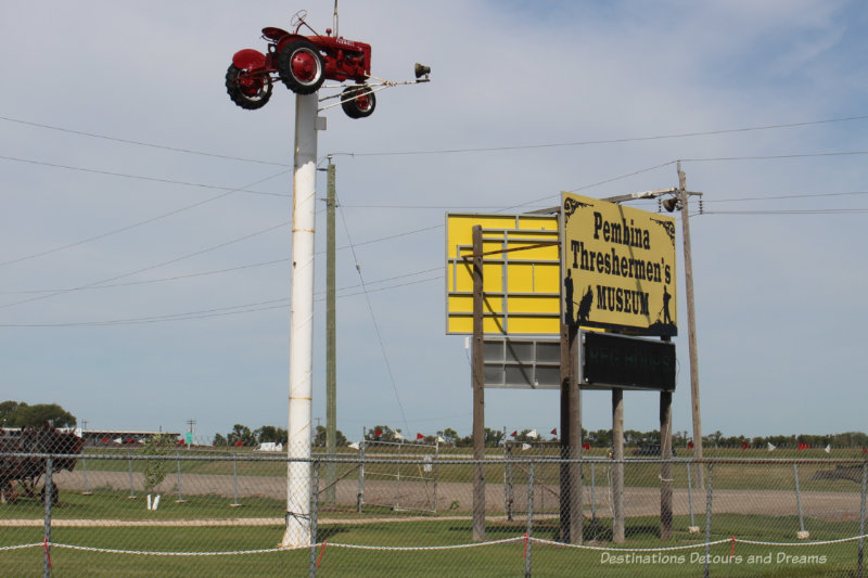 Pembina Threshermen's Museum sign beside a red tractor atop a pole