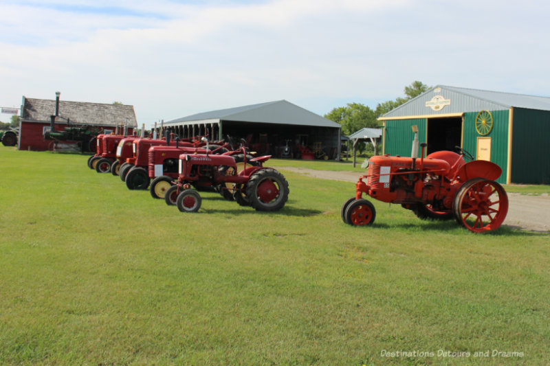 Red vintage tractors parked in a row in a field with several hangar type buildings in the background