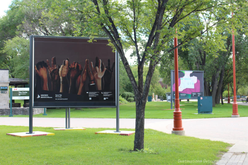 Two large paintings on billboards on opposite sides of a path through a park