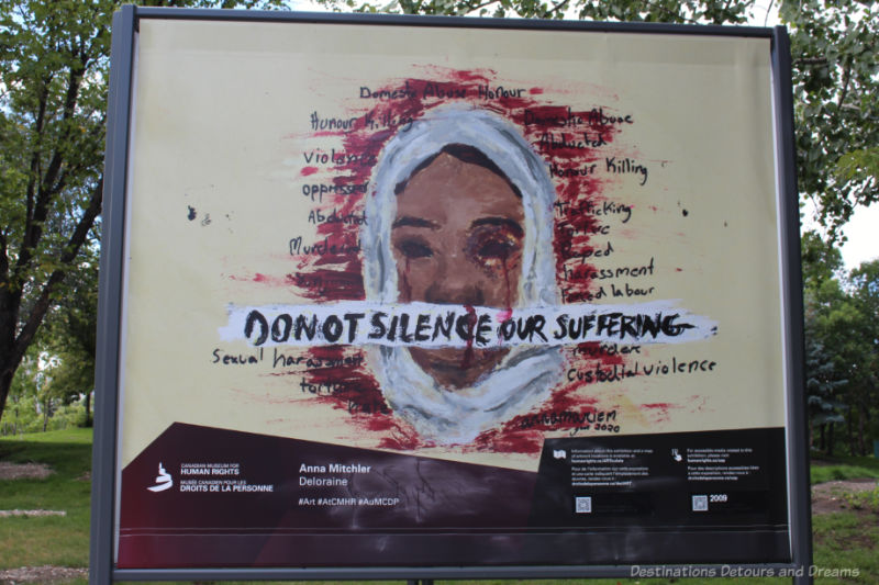 A painting of a dark-skinned woman in a white hijab crying red tears. A coloured area of red around her head contains words like oppressed and abducted; a white banner across her mouth read Do No Silence Our Suffering