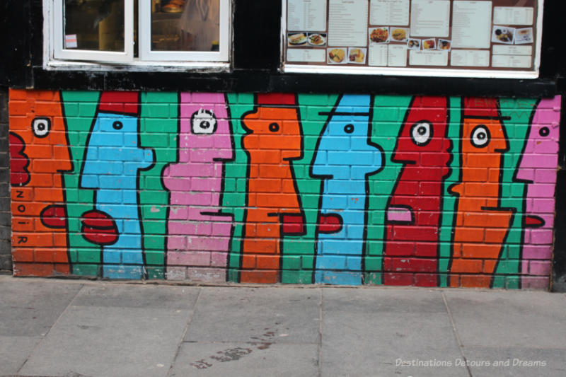London street art in Shoreditch: Stylized long skinny faces in orange, red, blue, and pink - streetart by noir
