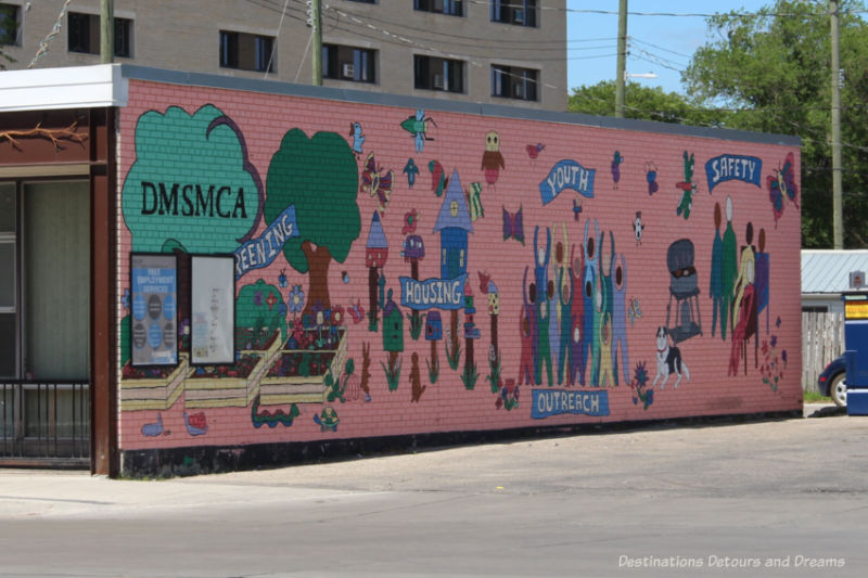 Mural on side of building with pink background and associated images associated with community needs of housing, outreach, and safety