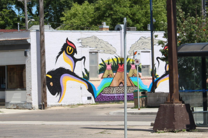 Indigenous style of art in a mural on the outside of building shows teepees and stylized animals