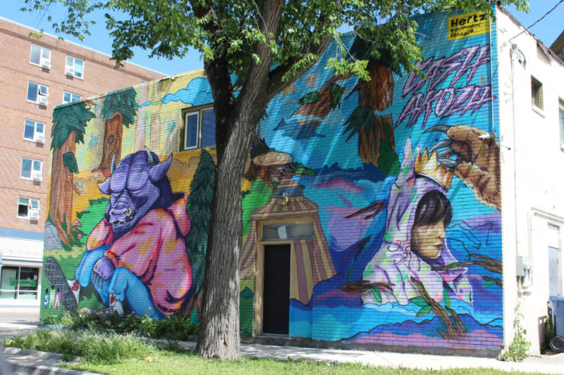 Mural in shades of blue, pink, and purple depicting a clothed animal with big ears and small horns in front of trees and woman with a colourful headscarf being crowned by a hairy hand with long talon nails
