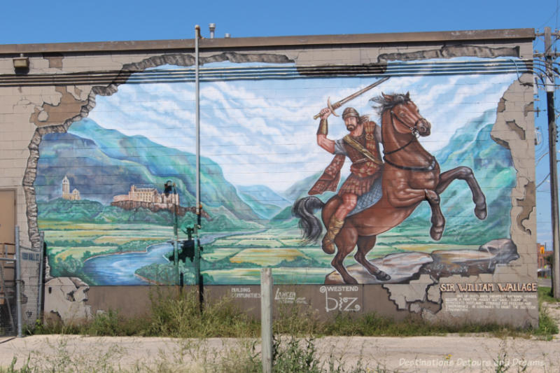 Mural featuring Sir William Wallace with sword on horse in Scottish landscape