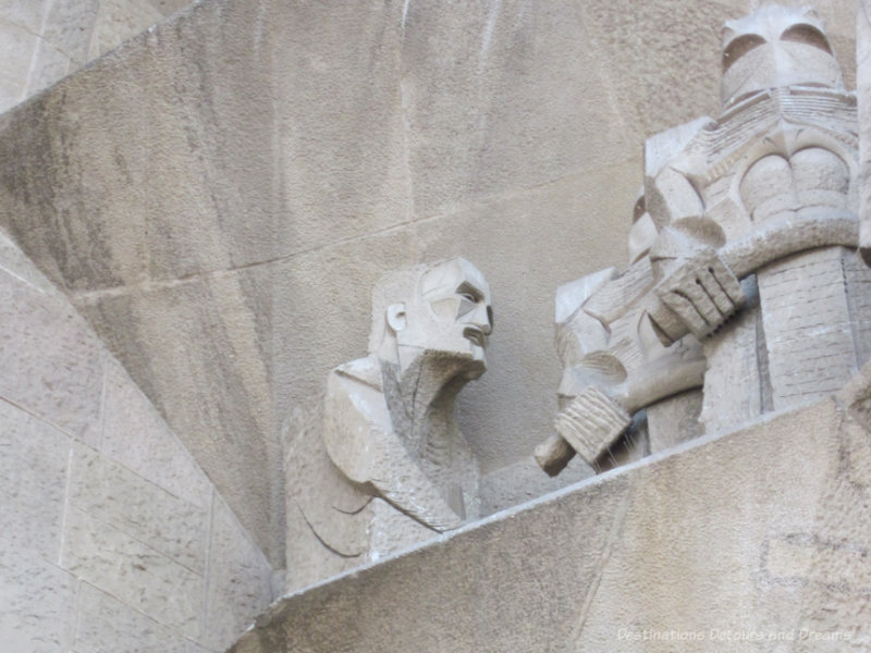 Stone sculpture of Gaudi on La Sagrada Família Passion Facade