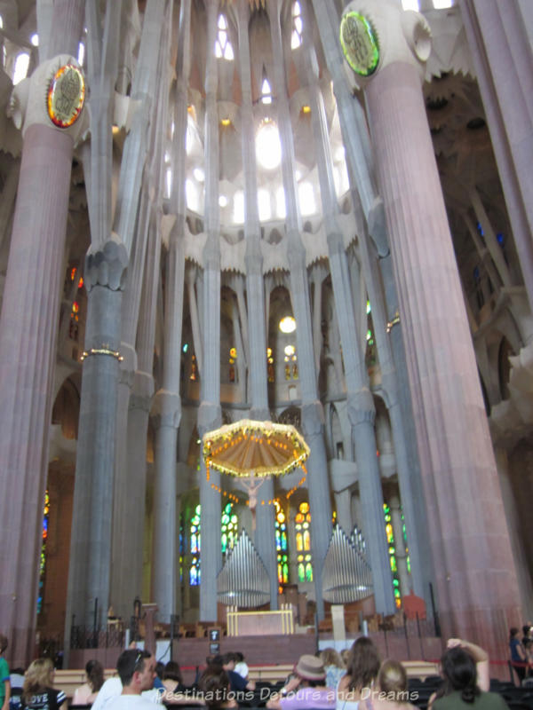 La Sagrada Família sanctuary amid tall stone pillars and light streaming through stained glass windows