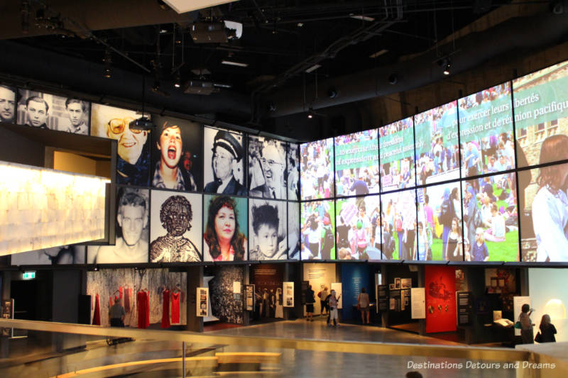 Looking down at niches of museum displays on the outside walls of a large room with images of people and human rights symbols projected on the tall walls above them at the Canadian Museum for Human Rights