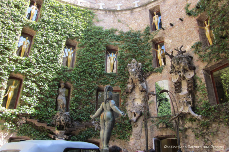 Ivy-covered brick wall in a circular courtyard with carved gargoyles and gold figurines in indented window ledges at the Dali-Theatre Museum