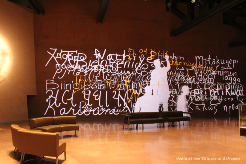 Projection of people writing welcome in many languages along a wall in a lobby