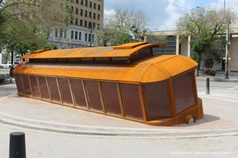 A public art piece in front on Winnipeg City Hall: a life-sized orange tilted trolley car