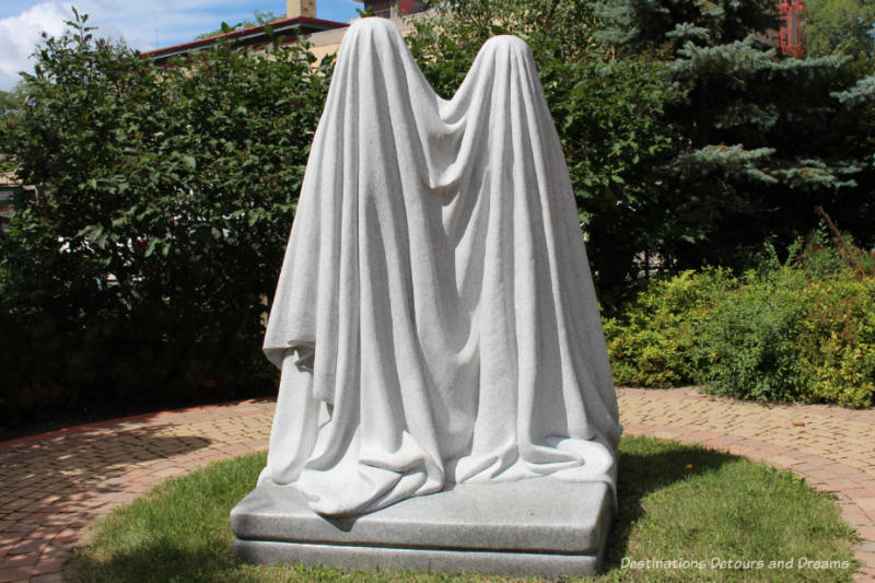 A Winnipeg public art piece featuring two stone figures draped in what looks like a white cloth