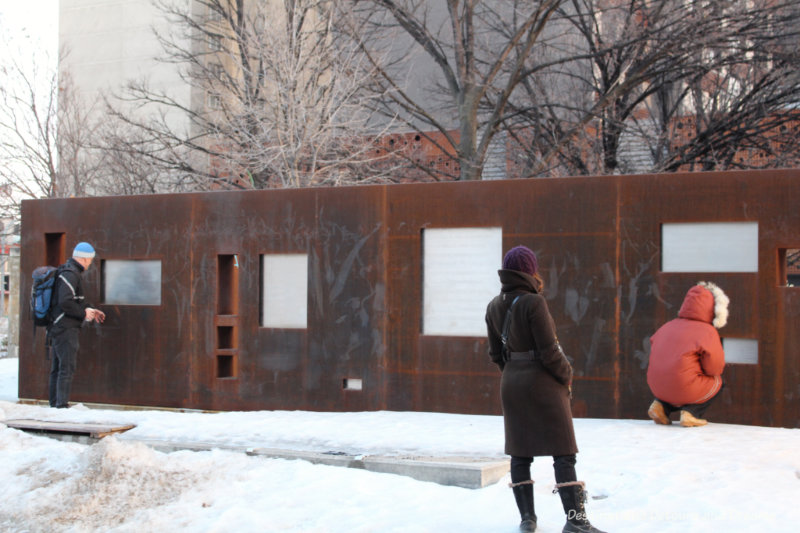 A Winnipeg public art piece consisting of wall of weathering steel with excerpts of text written on it