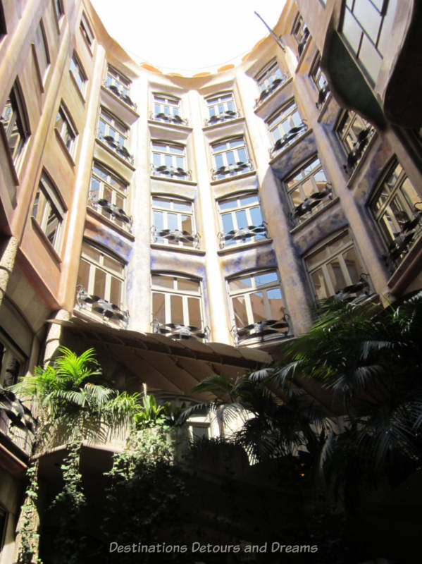 Looking up at the windows and ironwork balcony railings of Casa Milà apartments from the courtyard
