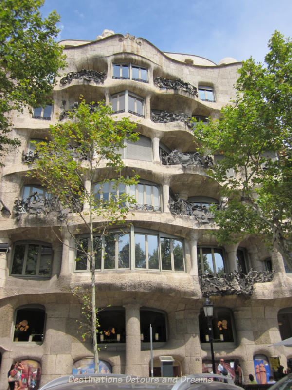 The rough-hewn stone wavy facade and wrought-iron balconies of Casa Milà in Barcelona